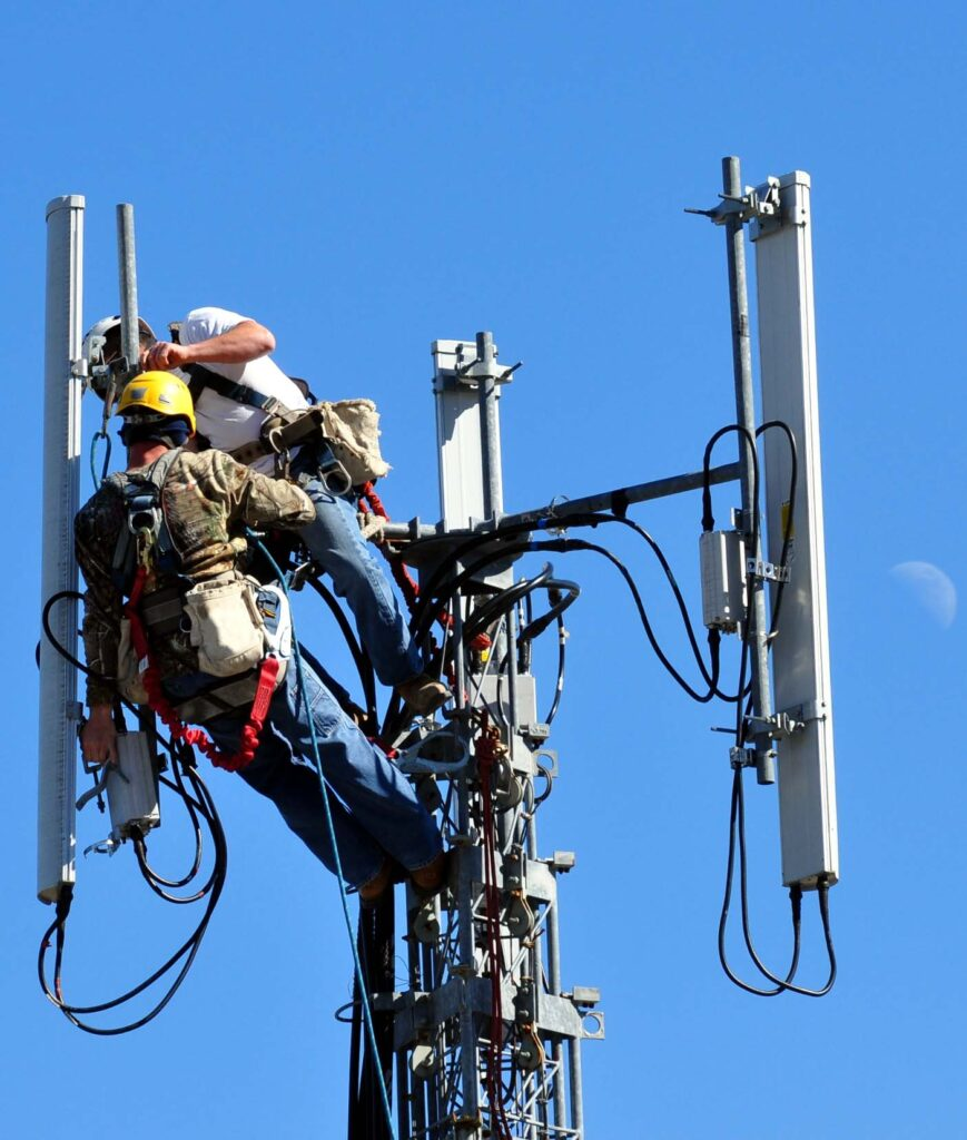 Workers maintaining a telecommunications tower used for mobile networks