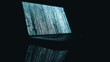 Image with a laptop displaying data scrambled by encryption